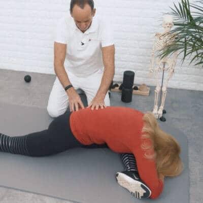 Eine Patientin mit Hüftblockade dehnt ihre Gesäßmuskulatur. Dazu liegt sie auf einer Matte, das linke Bein liegt in einem 90-Grad-Winkel vor ihr ab, während das rechte Bein ausgestreckt nach hinten genommen ist. Ihren Oberkörper legt die Frau dabei komplett auf der Matte ab. Schmerzspezialist Roland Liebscher-Bracht leitet sie an.