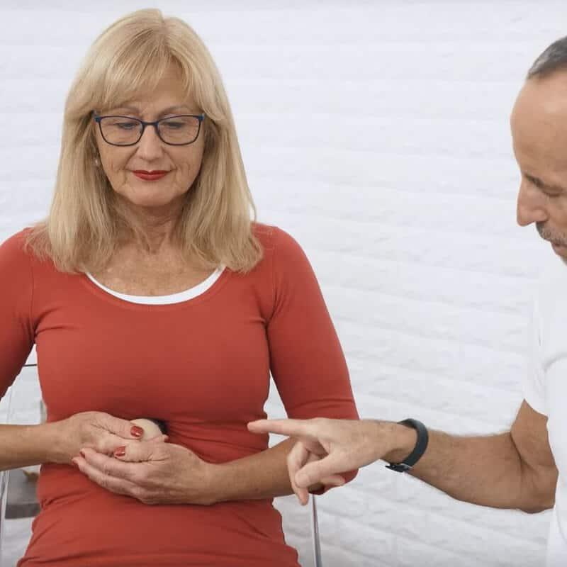 Eine Frau führt eine Light-Osteopressur gegen Sodbrennen mit dem Schmerzfrei-Drücker von Liebscher & Bracht durch. Roland Liebscher-Bracht achtet darauf, dass sie den Drücker an der korrekten Stelle am Schwertfortsatz platziert.