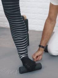 Eine Frau klammert sich mit den Zehen ihres linken Fußes an die Mini-Faszienrolle, um die Fußsohle bei einem Hallux valgus aufzudehnen