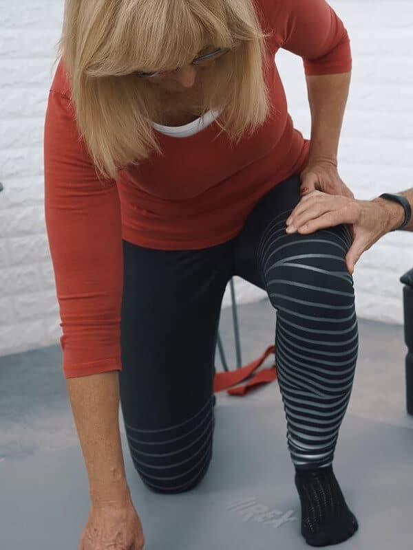 Eine Frau kniet sich mit dem rechten Bein hin und verlagert ihr Gewicht auf den linken Fuß, den sie auf der Matte aufgestellt hat, um die Fußsohle bei einem Hallux valgus zu dehnen