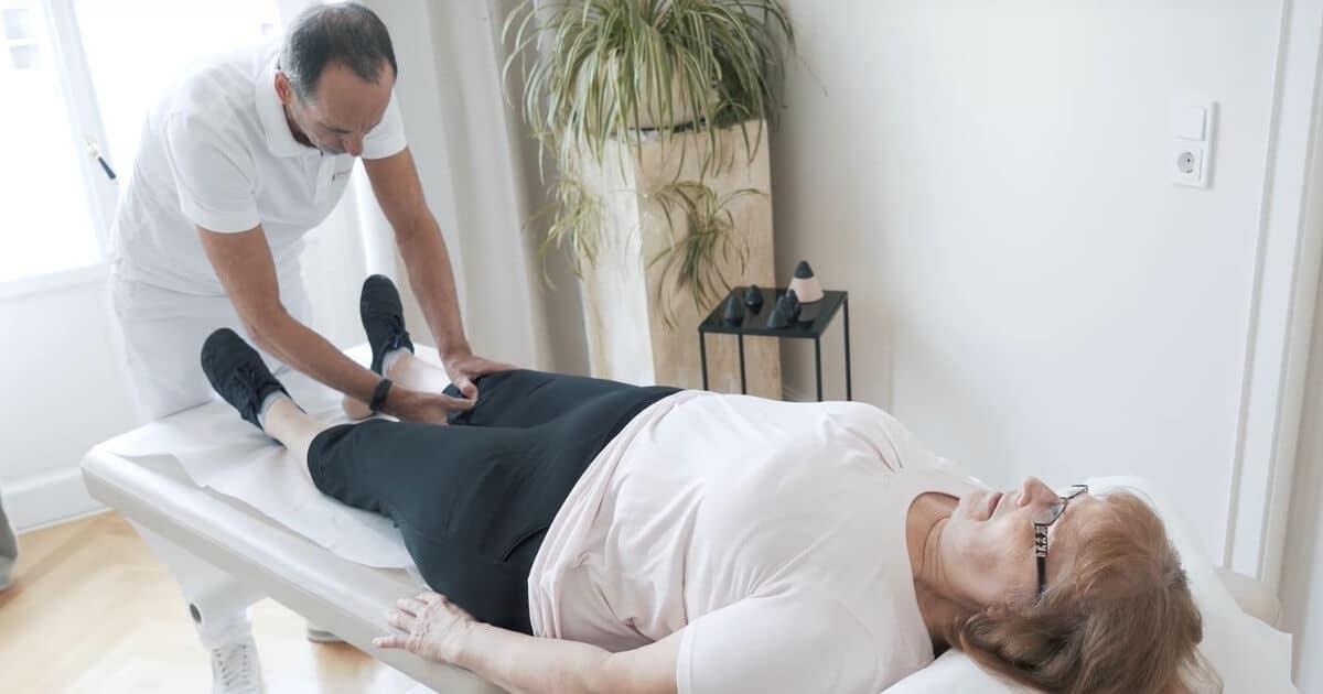 Roland Liebscher-Bracht wendet drückt bei einer Patienten einen Osteopressur-Punkt am Knie