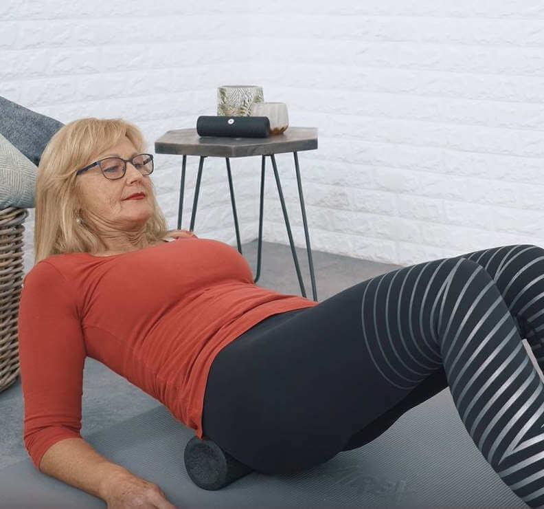 Eine Frau liegt mit ihrem Steißbein auf der Medirolle und stützt sich dabei mit ihren Armen auf einer Trainingsmatte ab, um den Rückenbereich damit abzurollen