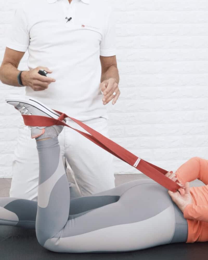 Eine Frau liegt auf einer Matte und zieht mit Hilfe der Übungs-Schlaufe ihr Bein zum Gesäß.
