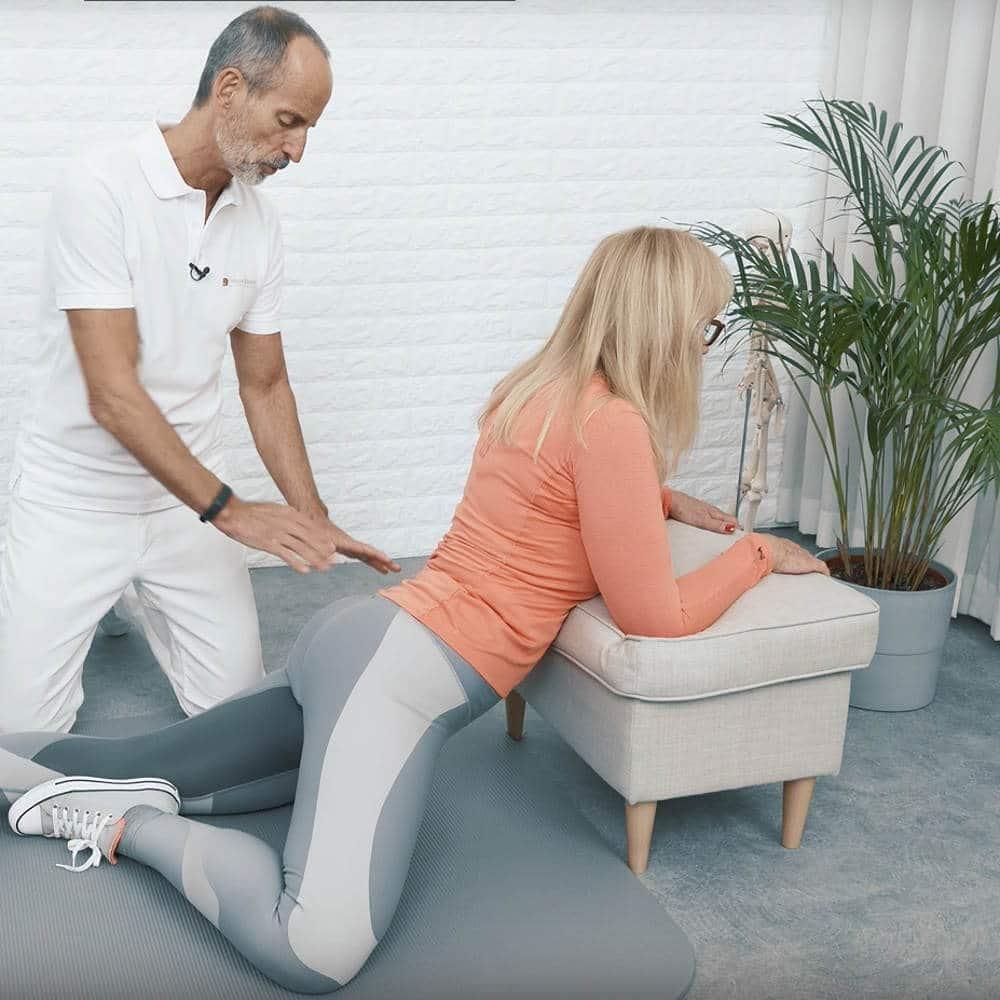 Eine Frau lässt ihre Leiste in Richtung Matte sinken und winkelt dabei ihr rechtes Bein an das linke Knie an, um ihre Rückenschmerzen loszuwerden, dabei überwacht ein Mann ihre Übungen.