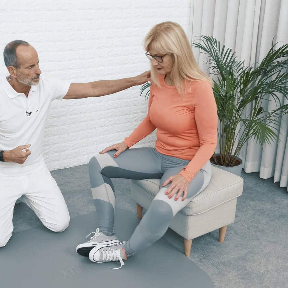Eine Frau sitzt auf einem Hocker, hat die Fußsohlen aneinander gewinkelt und lässt dabei ihre Knie nach außen fallen, um ihre Rückenschmerzen mit dieser Übung loszuwerden.