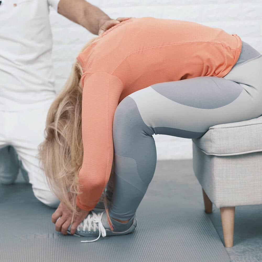 Eine Frau beugt sich im Sitzen nach vorne und umfasst ihre Fußzehen