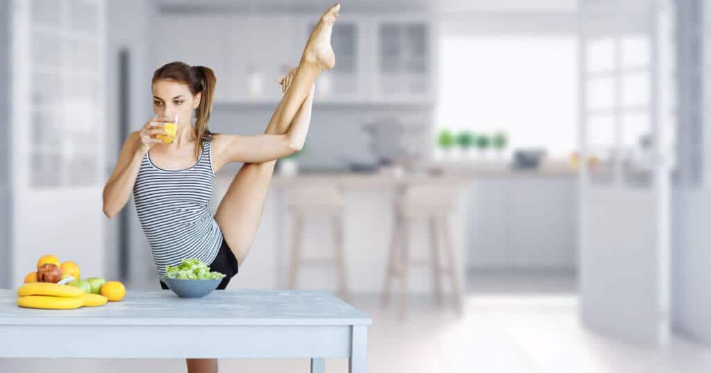 Eine Frau steht vor einem Tisch, auf dem Obst steht. Sie dehnt ihr Bein, indem sie es nach oben hoch zu ihrem Kopf haelt. Mit dem rechten Arm unterstuetzt sie die Position. In der linken Hand haelt sie ein Glas Orangensaft. Im Hintergrund ist eine Kueche zu erkennen.