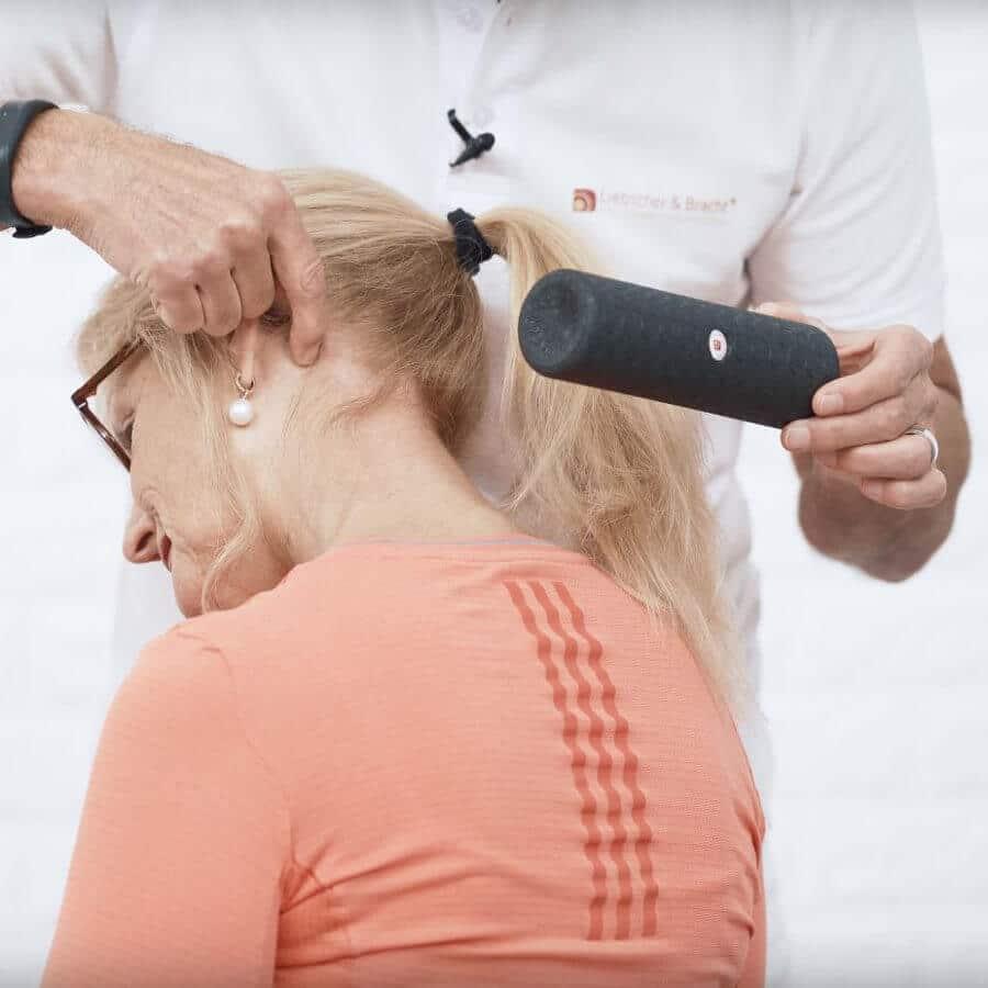 Roland zeigt Ina hinter ihrem linken Ohr den Punkt, an dem sie die Mini-Rolle gegen Nackenschmerzen ansetzen soll