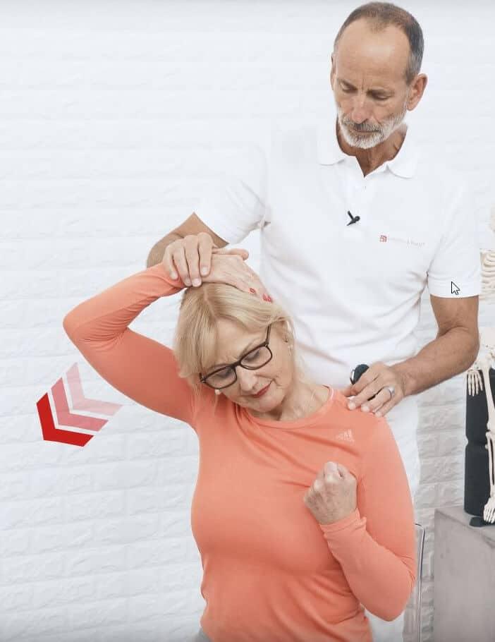 Ina führt eine Übung gegen Nackenschmerzen aus, indem sie ihren Kopf zur linken Seite neigt und ihn mithilfe ihres rechten Arms nach rechts unten zieht, um den linken Muskelstrang zu dehnen. Der linke Arm ist angewinkelt, die Hand zu einer Faust geballt