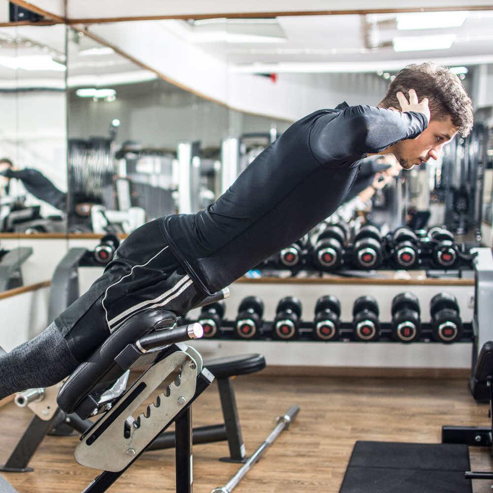 Ein Mann macht Rückentraining auf einem Fitnessgerät